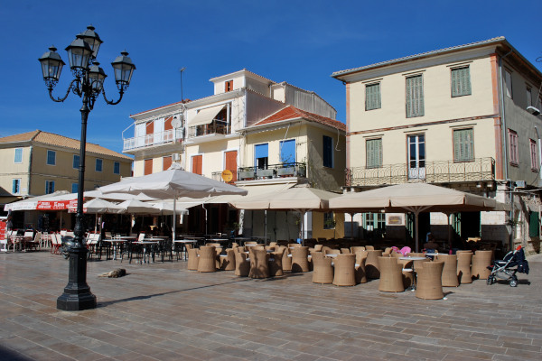 A photo showing a part of the Ethnikis Antistasis Square and some neighboring cafés in Lefkada Town.