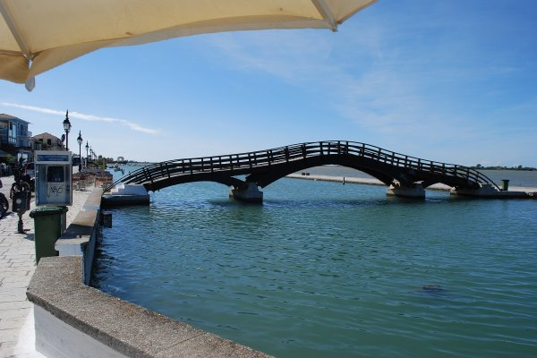 A photo of the Footbridge of Lefkada Town during the sunset with many people standing on it.
