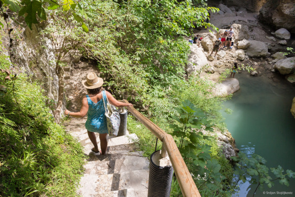 A photo showing the turquoise lake of Nidri Waterfalls on Lefkada and a woman on the steps leading to that.