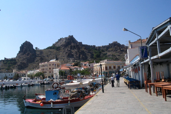 The seafront promenade that includes a part of the port and the hill of the castle in the background.