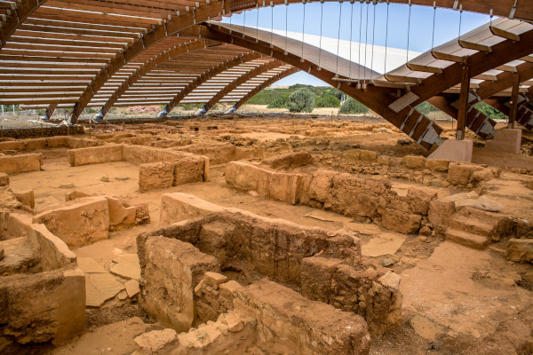 The remains of the Archaeological Site of Malia under a protective overhanging ceiling.