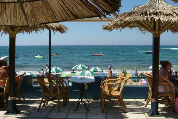 A photo taken from a veranda of a beach bar showing the Malia Beach.