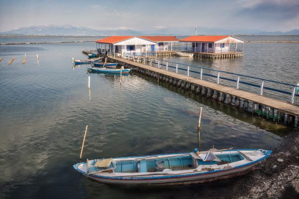 Fishing huts, a bridge and a boat in the lagoon of Mesolongi.