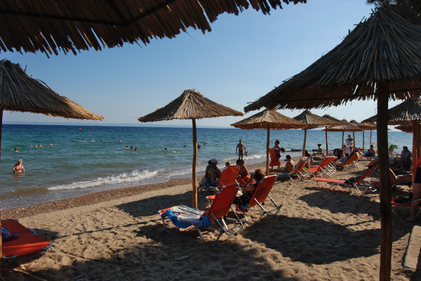 A photo of the Metamorfosi beach of Halkidiki taken between the umbrellas and sunbeds of a local beach bar.