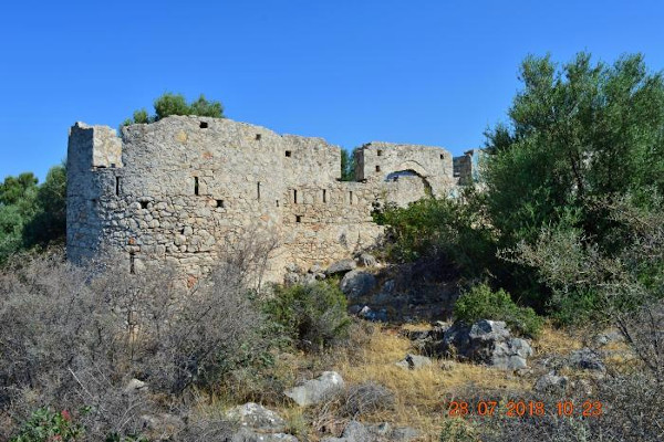 A photo of the Favieros Castle at Methana amid bushes and trees.