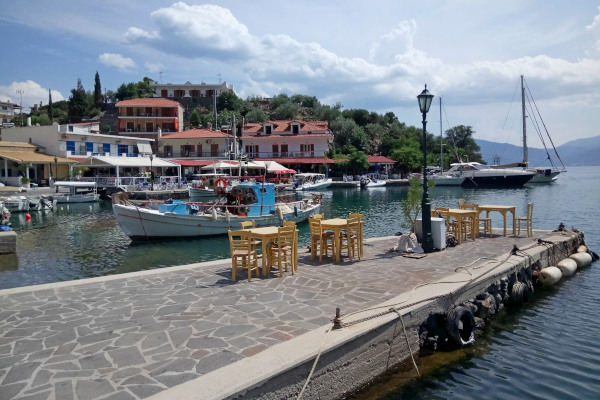 A part of the pier of the Vathi port at Methana with some tables of the nearby restaurants.