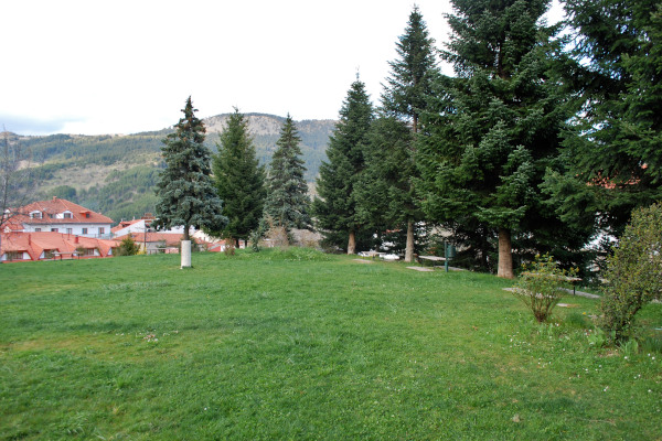 A part of Averofeios Garden in Metsovo where the green grass and the surrounding trees dominate the landscape.