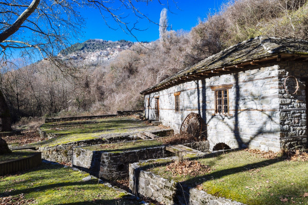 The stone-built building and the front yard of Gina's Watermill of Metsovo.