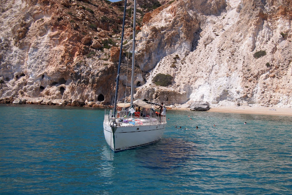 A sailing boat by the rocky cliffs off the coast of Milos Island.