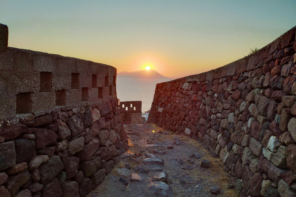 The spectacular sunset of Milos between the walls of the Venetian Castle in Plaka.