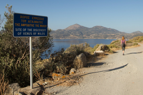 A sign at a rural road that informs about the area of the discovery site of the Venus of Milos.