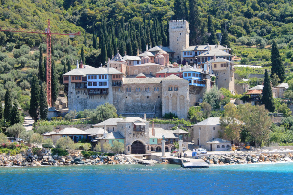 The seafront, the churches, the facilities, and the dense vegetation in the background of Docheiariou Monastery.