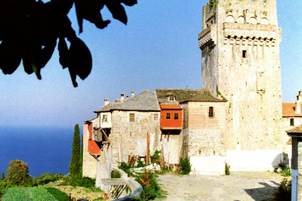 The outer walls and the defensive tower of Karakallou Monastery with the deep blue sea-view in the background.