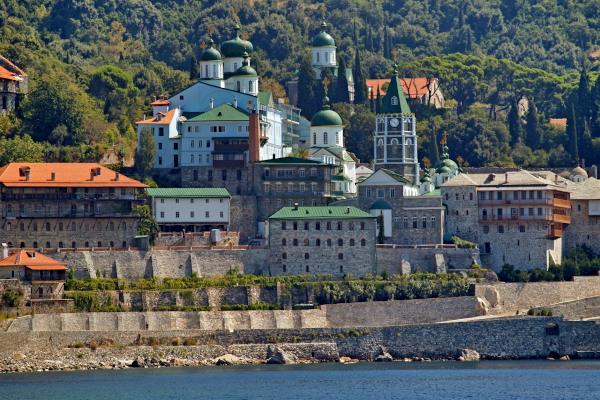 A view of Saint Panteleimon Monastery which is located at the coastline of an area with dense vegetation.