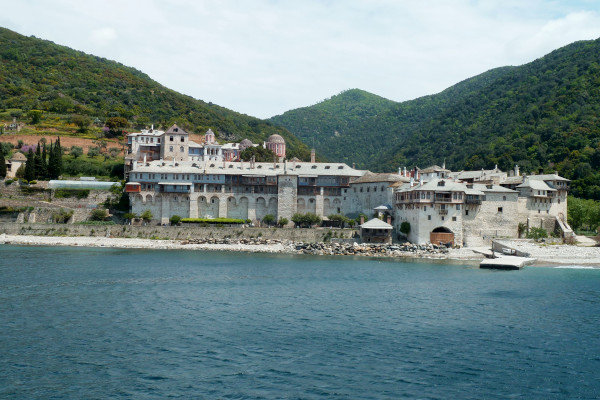 A picture of Xenophontos Monastery taken from the sea showing the seafront and the dense vegetation in the background.