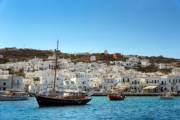 Sailing tourist boats in the port of Mykonos with the buildings of the main settlement in the background.