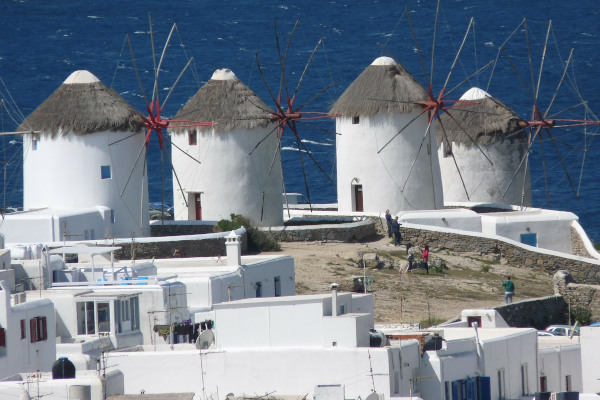 A close up image showing the Windmills of Mykonos with the blue Aegean Sea in the background.