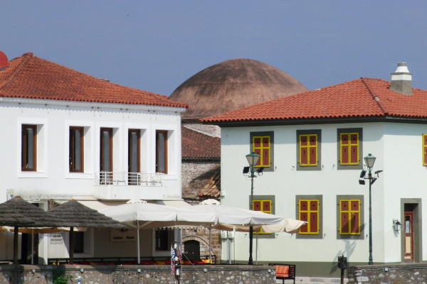 The building of Fethiye Mosque of Nafpaktos can be seen behind two other buildings.