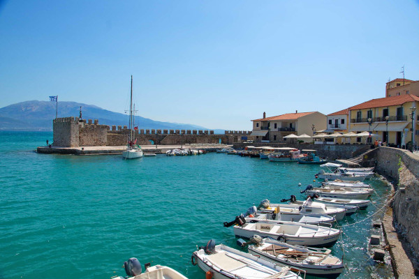 A photo showing the fortified port of Nafpaktos with many small boats anchored by the coast.
