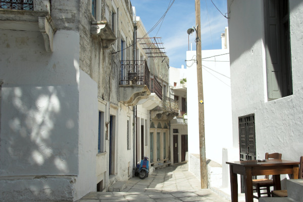 A central narrow street of the Apeiranthos village in Naxos with the totally white surrounding buildings.