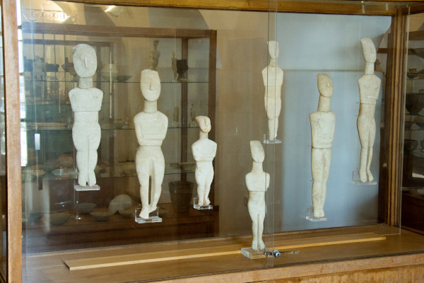 Seven Cycladic figurines in a display of the Archaeological Museum of Naxos.