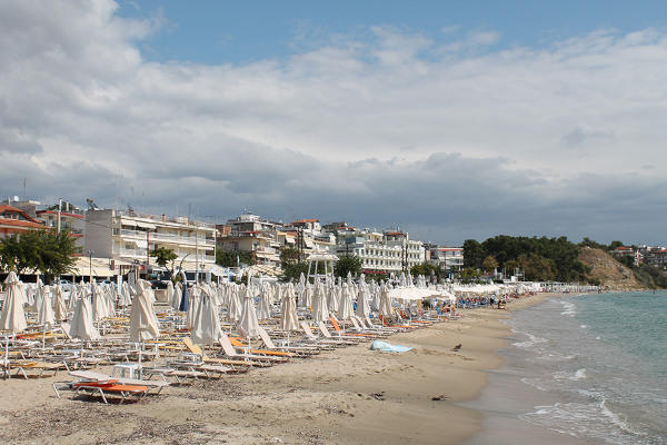 Numerous umbrellas and sunbeds on the beach of Nea Kalliktatia beach.