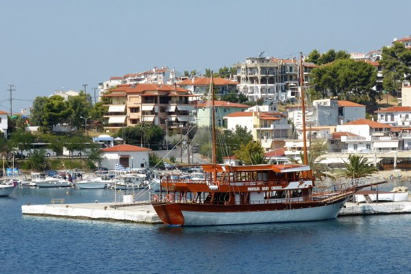 A day-trip cruise ship anchored by the pier of the Port of Neos Marmaras.