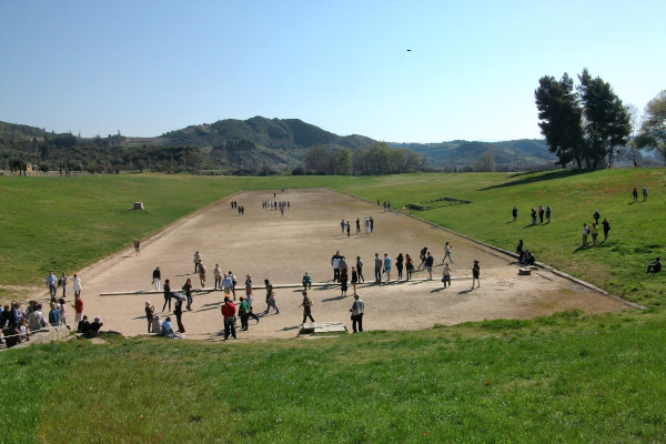 An overview of the Ancient Olympia Stadium with many visitors hanging around.