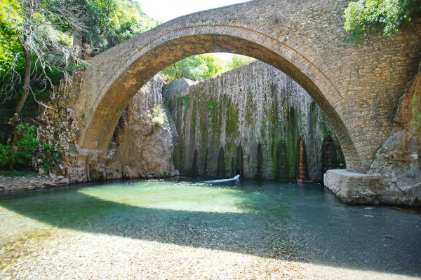 The stone-built arched bridge and the waterfall of Palaiokaria in the background.