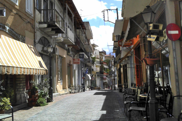 A pedestrian street with shops, boutiques, and cafeés in the commercial center of Paramythia.