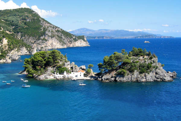 A picture of the Islet of «Virgin Mary» of Parga with a chapel surrounded by blue sea.