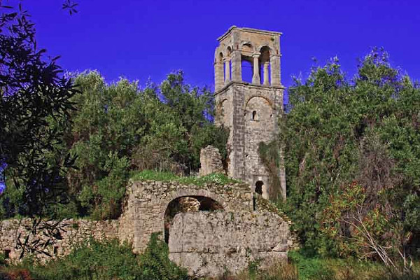 The belfry and other ruins of the Vlacherna Monastery of Parga among dense vegetation.