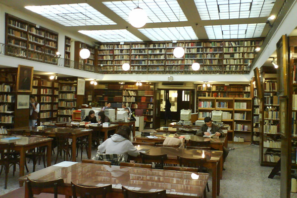 People surrounded by bookshelves are reading on tables of a room of the Municipal Library of Patras.