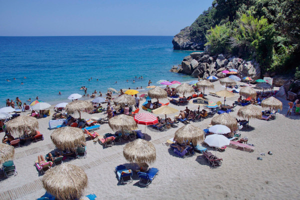 Many people, umbrellas, and sunbeds at one part of the Agii Saranta beach of Zagora on Pelion.