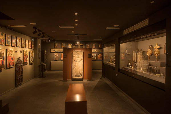 Inside one of the rooms of the Byzantine Museum of Makrinitsa with artifacts in displays and icons hanging on the walls.