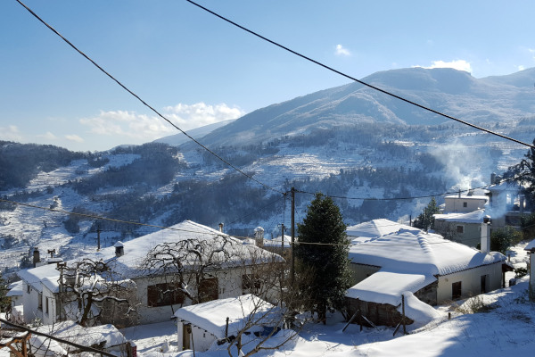 Some of the snow-covered houses of Zagora in Pelion with the mountain in the background during a  sunny day.