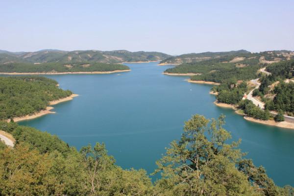 An overview of the Plastira lake among hills of dense vegetation.