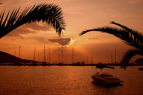 A picture showing a tourist boat and many other sailing boats in the marina of Plataria during an evening.