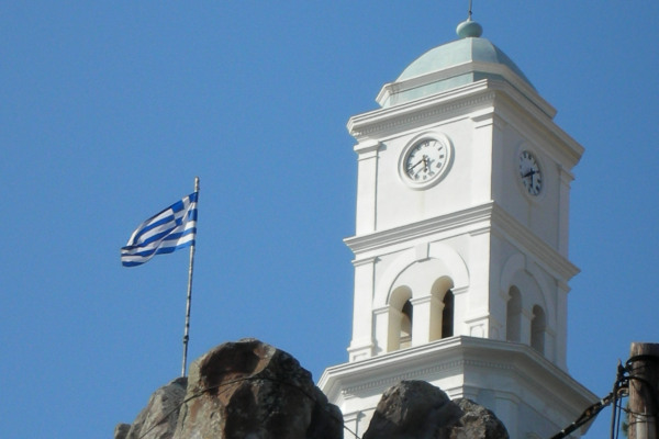 The Clock Tower of Poros next to the Greek flag.