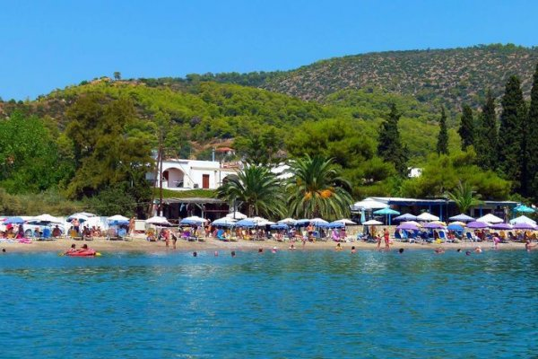 A picture showing many people, sun beds and umbrellas at the Kanali Beach of Poros.