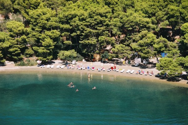 An aerial photo showing the Love Bay Beach on Poros and people swimming in its blue-green waters.