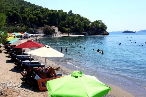 A photo showing umbrellas, sun beds and people enjoying at the Monastiri Beach of Poros.