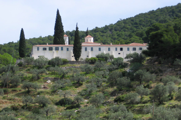 A picture of the exterior of the «Zoodohos Pigi» Monastery in Poros among the lush vegetation.