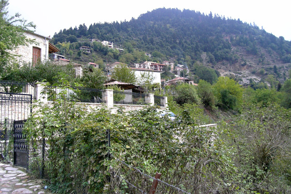 A picture showing some houses and the mountain as a background at the village of Megalo Chorio.