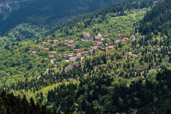 Picturesque old settlement of Old Mikro Chorio among the dense vegetation of the mountainous Eyritania area.