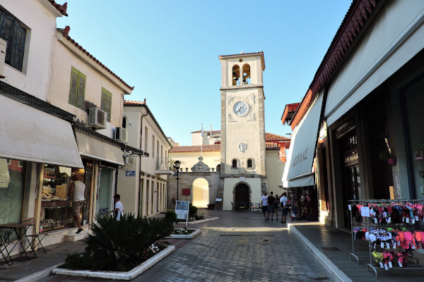 The Venetian Clock & St. Charalampos Church of Preveza at the end of a pedestrian street with shops and boutiques.