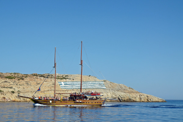 Cruise ship by the coast of Pserimos island and the Greek flag that was drawn on the land.