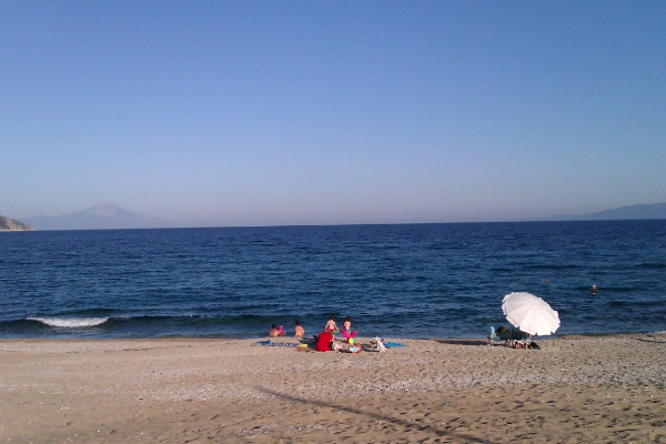 A photo depicting a family to enjoy the sun and the water at the Kampos (Ladhario) beach of Pyrgadikia.