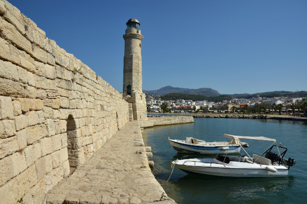 The Lighthouse of Rethymno at the old port of Rethymno with a part of the city in the background.
