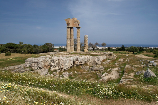 Remains of the temple of Apollo at the Acropolis of Rhodes on a grassy hill.